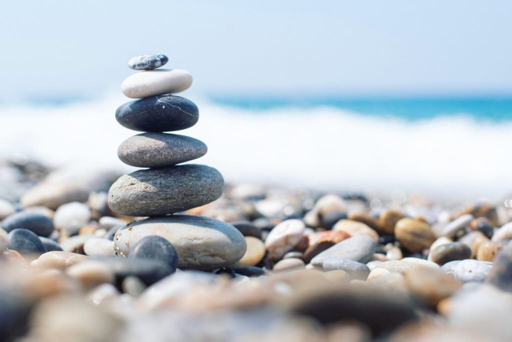 A picture shows rocks stacked on the beach. This demonstrates concepts of online anxiety treatment in Chicago, IL with Equipoise Teletherapy.