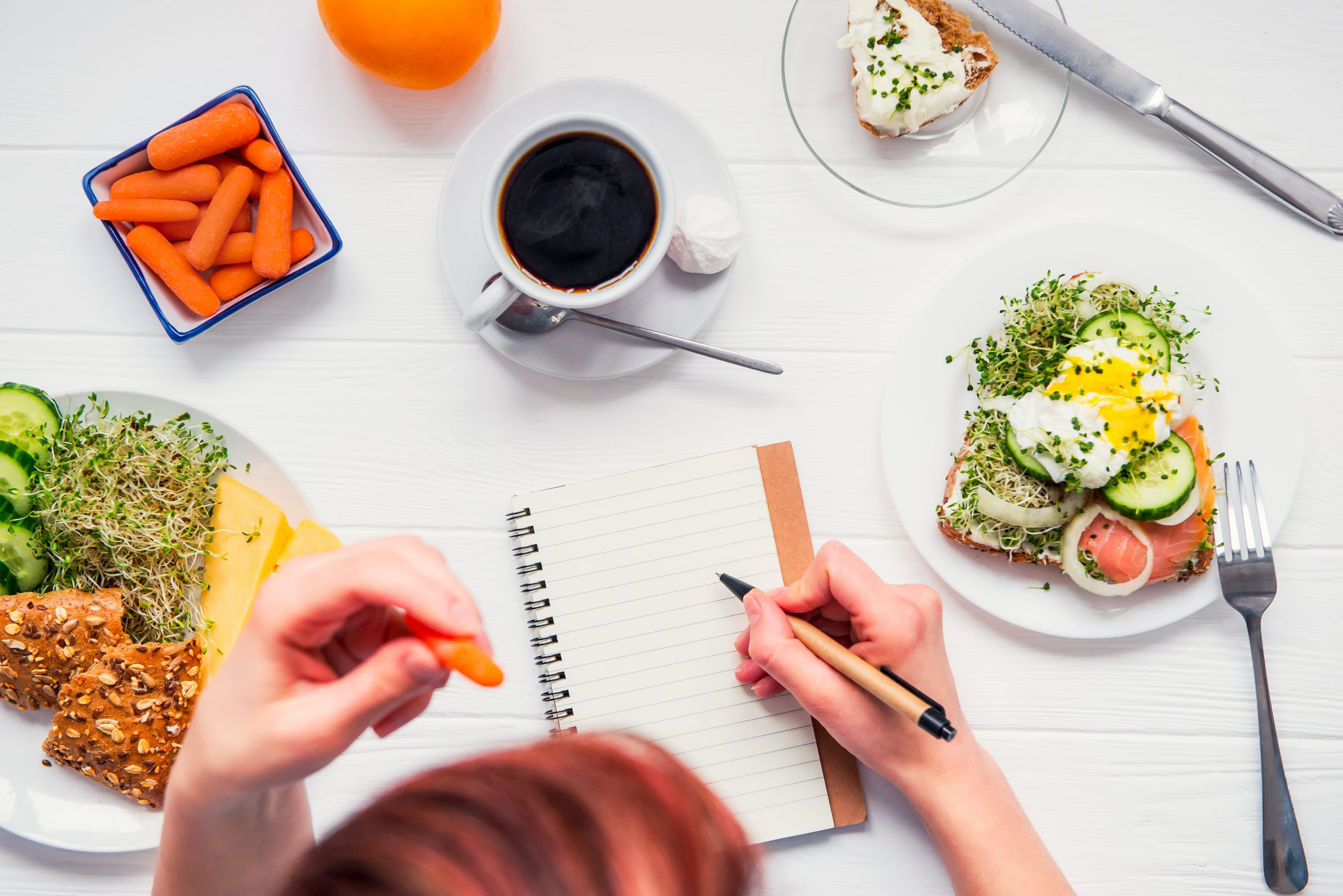 Top down view of woman writing in her journal as she eats from the plates of food around her. Equipoise Teletherapy offers medicial nutrition therapy in chicago, il, intuitive eating counseling in chicago, il, and more.