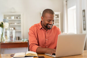 A man smiles as he types on his laptop. This symbolizes the convience of online thearpy in Virginia. Contact an online therapist in Virginia for support with online addiction treatment, intuitive eating counseling, and other services.