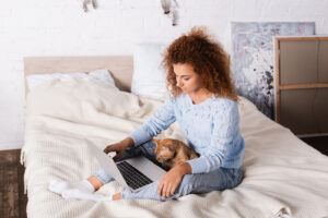 A women sits on her bed with a laptop and puppy. This represents how online therapy in Virginia can occur anywhere! Learn more about our services from an online therapist in Virginia, we offer online thearpy in pennsylvania and more!