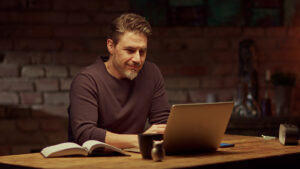 A man sitting at the kicthen counter smiles as he looks at his laptop. This could represent online thearpy in Virginia. An online therapist in Virginia can offer you support from the comfort of home. Learn more about online thearpy in Illinois, Texas, Pennsylvania, and more!