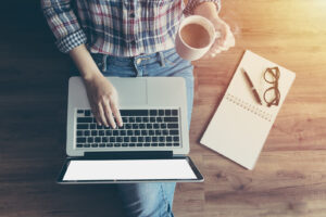 A person sits on a wooden floor as they type with coffee in hand. This could represent the convience of online therapy in Texas. Contact an online therapist to learn more about our services!