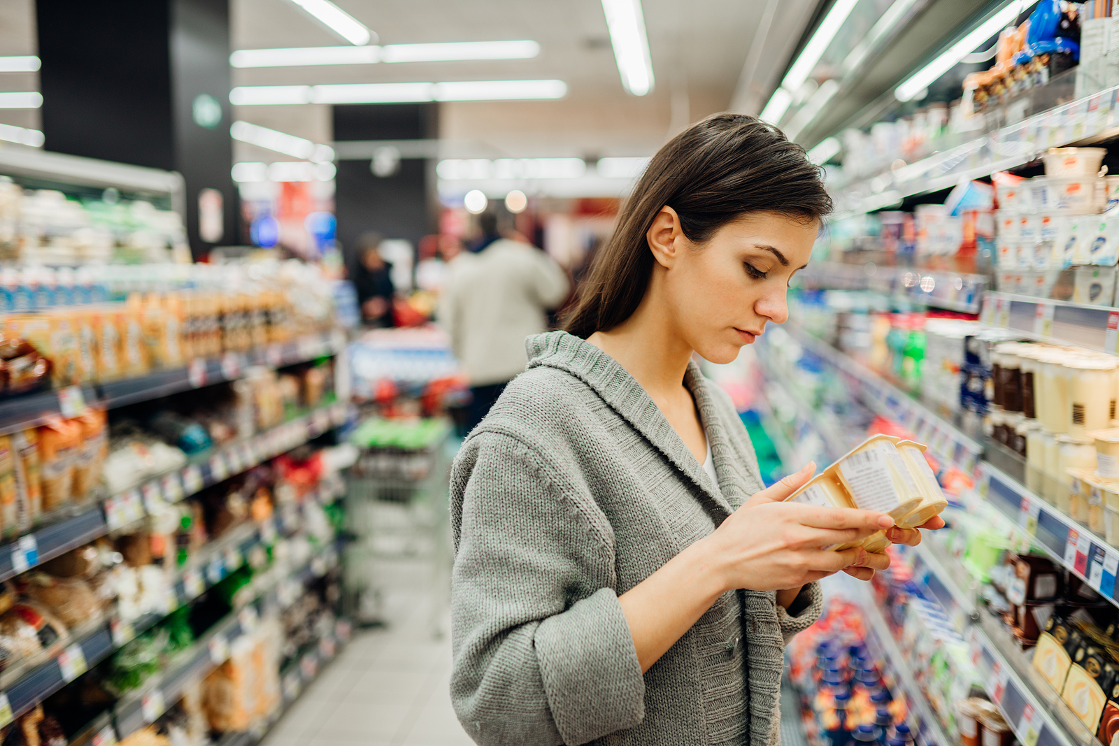 young woman stands in the aisle as she shops for food. She is going over the nutrition facts, and is frustrated that she never knows what foods might be good for her diet. Equipose Teletherapy offers online nutrition counseling in chicago, il, intuitive eating counseling in chicago, il, and more. Contact us today to get in contact with an online nutritionist in Illinois