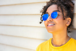A woman is wearing sunglasses. This represents concepts often discussed in online therapy. Online therapy for PSYPACT states allows PSYPACT providers to work with individuals in many different states.