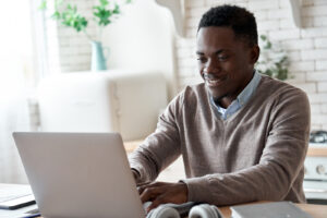 A person uses a laptop. This is a step some people take before starting online therapy in PSYPACT states. Online therapy allows them to work with many PSYPACT providers that are online therapists.