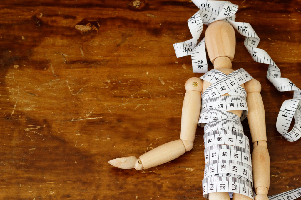 A wooden figure lays with a tape measure wrapped aroundtheir body. This could represent binge eating disorder treatment in Chicago, IL. Learn more about online binge eating disorder treatment in Chicago, IL