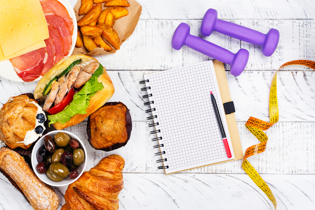 Top down image of various foods, hand weights, and measuring tape for Equipose Teletherapy. We offer treatment for disordered eating in Chicago, Il, online eating disorder therapy in georgia, and more. Contact us today for nutritional therapy today!