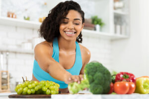 Smiling African American woman reaches for a piece of broccoli next to other fruits and vegetables after learning about intuitive eating with her haes therapist in Chicago, IL. She has never felt more in tune with her body than after disordered eating treatment in Chicago, IL. Equipoise Teletherapy offers treatment for disordered eating, online eating disorder therapy in Nevada, and more. Contact us to get in touch with an eating disorder therapist in Chicago, IL